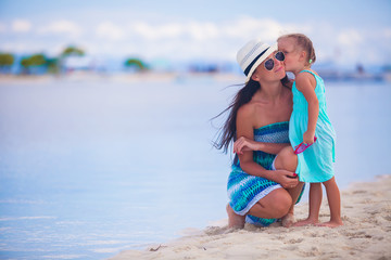 Little girl kissing her beautiful mother on a white tropical