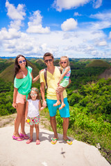 Young family of four on a background of the Chocolate Hills in