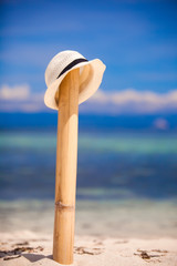 Straw hat at wooden fence on the white sandy beach with an ocean