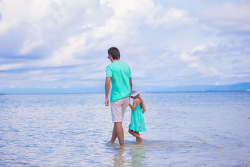 Back view of young father and his little girl walking by the sea