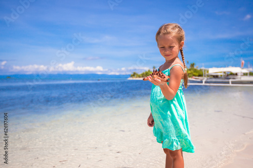 Little adorable girl with starfish in her hands at the tropical