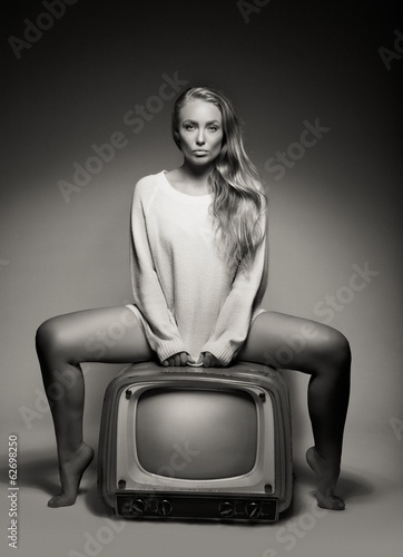 Sexy young woman sitting on a TV