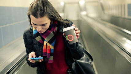 Young woman with smartphone and coffee riding escalator