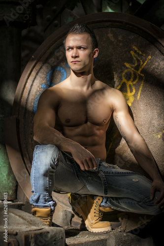 Muscular shirtless young man in abandoned industrial warehouse