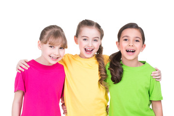 Three cute little cute smiling girls in colorful t-shirts.