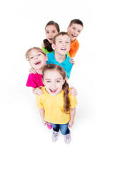 Group of children in colorful t-shirts standing.