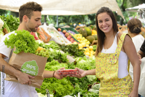 Couple shopping organic fruits and vegetables.