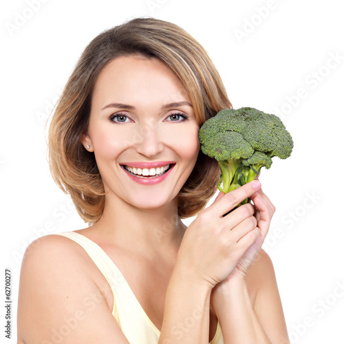 Beautiful young healthy woman holds broccoli.