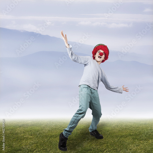 boy with clown nose and hat outdoors