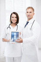 two doctors showing x-ray on tablet pc
