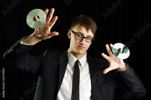 Young man in suit holding two compact discs
