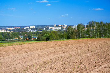 spring landscape with the city and the opened field