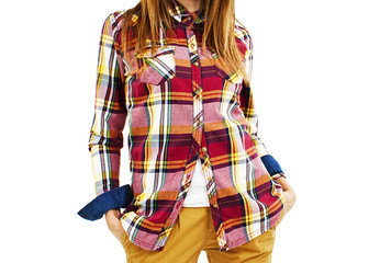 Young fashion woman in plaid shirt and hands in pockets