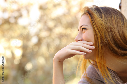 Happy woman laughing covering her mouth with a hand