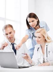 doctors looking at laptop on meeting
