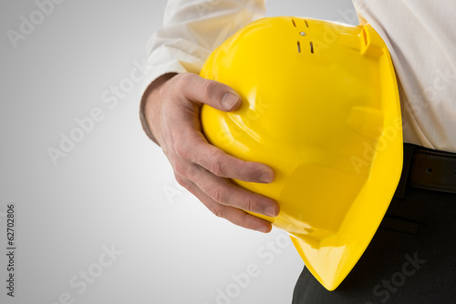 Professional man carrying a yellow hardhat