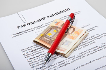 Partnership agreement forms with Euro money and pen