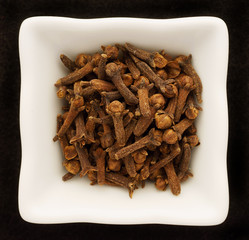 Spice cloves in a ceramic bowl. Isolated on black.