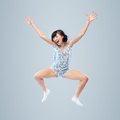 Funny girl in pajamas jumping for joy