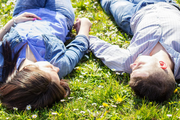 Young couple lying on the grass and holding hands