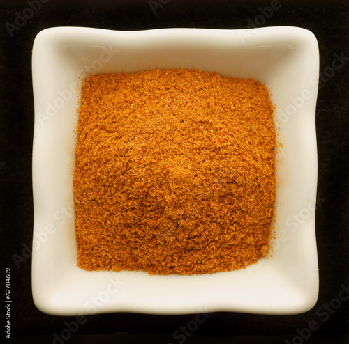 Spice curry in a ceramic bowl. Isolated on black.