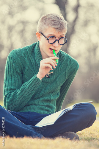Funny student with pen on a grass