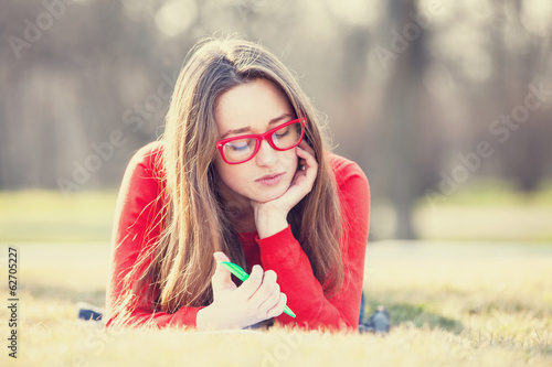 Teen girl with a pen lying down on a grass.