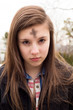 Teenage girl with cross for Ash Wednesday on forehead