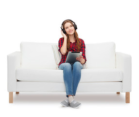 girl sitting on sofa with headphones and tablet pc
