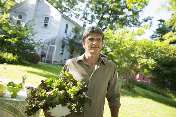 On The Farm. A Man In A Farmhouse Garden, Carrying A Large Bowl Of Freshly Picked Organic Lettuce And Salad Leaves.