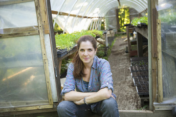 On The Farm. A Woman Sitting Resting At The Door Of A Glasshouse With Benches Full Of Young Seedling Plants.