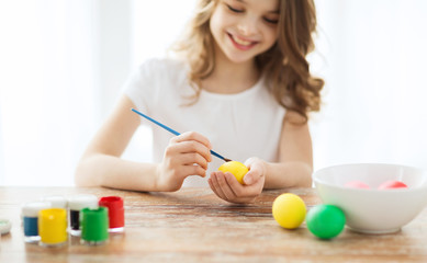 close up of girl coloring eggs for easter