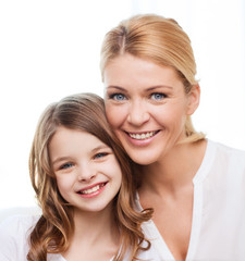 smiling mother and little girl at home