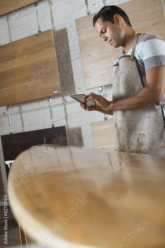 A Young Man In A Workshop. Using A Digital Tablet To Keep Records And Photograph Objects.