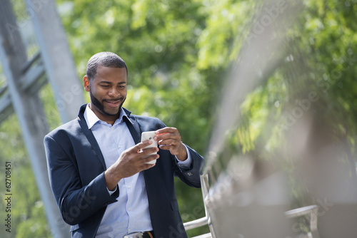 Summer. A Man In A Blue Jacket And Open Necked Shirt. Using A Smart Phone.