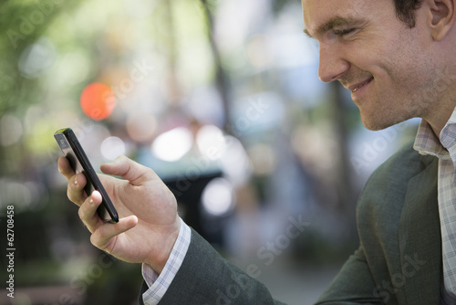 Summer. A Young Man In A Grey Suit. Using A Smart Phone.