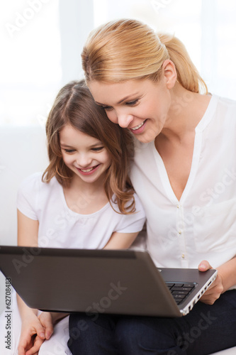 smiling mother and little girl with laptop at home