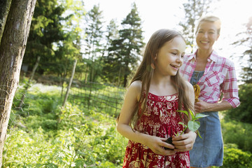 A Young Girl Holding A Seedling Plant, And Walking Through The Gardens Of The Farm With An Adult Woman Following.