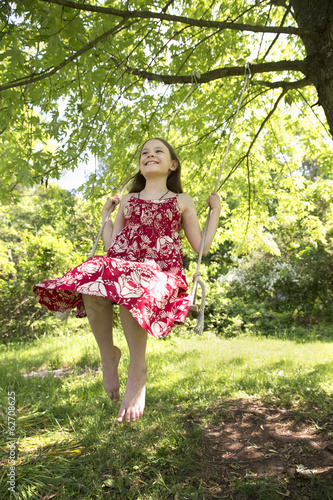 Summer. A Girl In A Sundress On A Swing Swinging From The Bough Of A Leafy Tree.