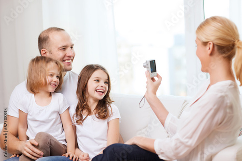 mother taking picture of father and daughters