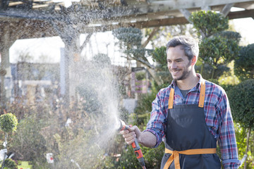 gardener watering potted trees in a garden center