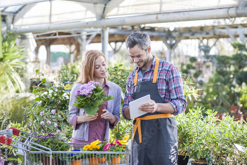 gardener using his digital tablet to advise a female client who - 62709660