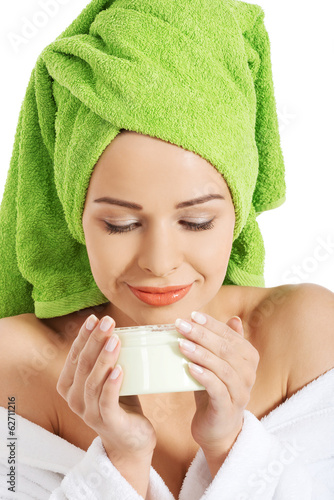 Woman in bathrobe with cream