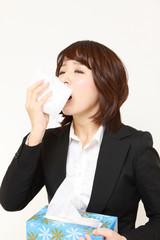 くしゃみと鼻水が止まらないアレルギー性鼻炎のビジネスウーマン
