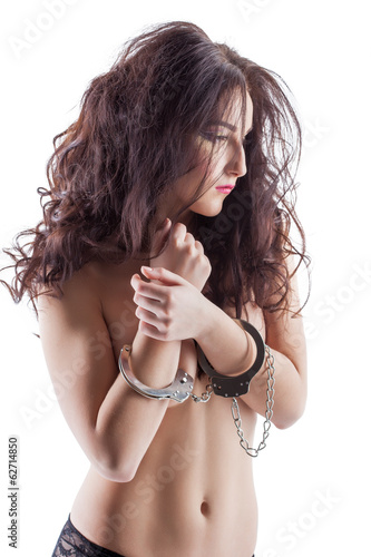 Image of slender model posing topless in handcuffs