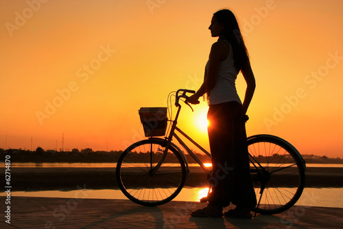 Silhouetted woman with bicycle at Mekong river waterfront at sun