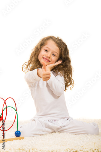 Happy little girl gives thumbs