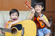 little sibling boy playing guitar and ukulele happy face - 62717232