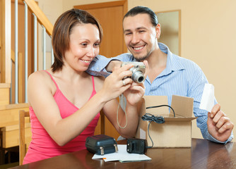 Happy couple unpacking new  camera