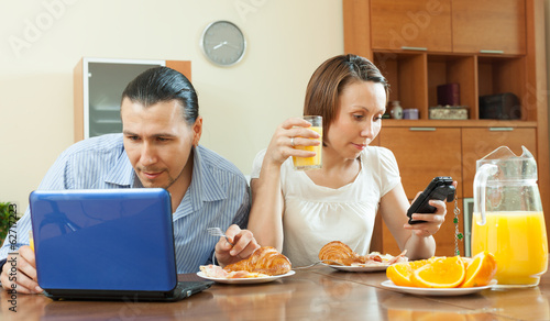 Couple using devices during breakfast time